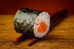 Maki sushi roll on chopsticks. Closeup detail of maki sushi roll on chopsticks stock images