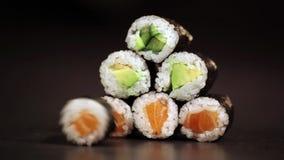 Maki sushi rolls on black background. stock footage