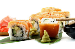 Maki Sushi. With Salmon, Crab, Avocado and Cheese on Green Palm Leafs with Wasabi, Ginger and Pair of Chopsticks closeup on White background stock photo
