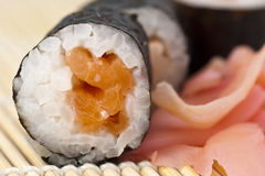 Maki Sushi. Salmon maki sushi and pickled ginger on a bamboo mat stock photos