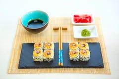 Maki Sushi With Sea Fish y queso cremoso en la tabla Cocina japonesa El sushi del rollo fijó en un tablero negro de la pizarra Fotografía de archivo libre de regalías
