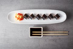 Maki sushi served in long plate on grey table stock photos
