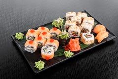 Maki Sushi stellte auf dunklen Musterhintergrund ein Gesetztes nigiri, Rollen und Sashimi der Sushi dienten in der schwarzen quad lizenzfreie stockfotos