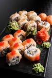 Maki Sushi stellte auf dunklen Musterhintergrund ein Gesetztes nigiri, Rollen und Sashimi der Sushi dienten in der schwarzen quad stockfoto