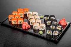 Maki Sushi stellte auf dunklen Musterhintergrund ein Gesetztes nigiri, Rollen und Sashimi der Sushi dienten in der schwarzen quad lizenzfreies stockbild