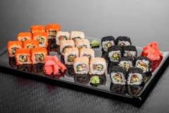 Maki Sushi stellte auf dunklen Musterhintergrund ein Gesetztes nigiri, Rollen und Sashimi der Sushi dienten in der schwarzen quad stockbild