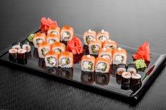 Maki Sushi stellte auf dunklen Musterhintergrund ein Gesetztes nigiri, Rollen und Sashimi der Sushi dienten in der schwarzen quad lizenzfreie stockbilder