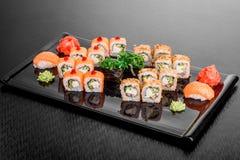 Maki Sushi stellte auf dunklen Musterhintergrund ein Gesetztes nigiri, Rollen und Sashimi der Sushi dienten in der schwarzen quad lizenzfreie stockfotografie