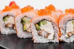 Maki Sushi stellte auf dunklen Musterhintergrund ein Gesetztes nigiri, Rollen und Sashimi der Sushi dienten in der schwarzen quad stockfotografie