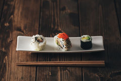 Maki sushi variety. Fresh and delicious maki sushi with its chopsticks. Vintage edition Royalty Free Stock Image