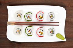 Maki sushi on white plate with chopsticks. Royalty Free Stock Photography