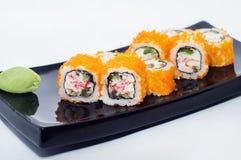 Maki sushirullar med avokadot, lax och kaviar och krabbakött Arkivfoton