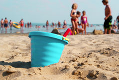 Makig sandcastles on the beach. A family is making sandcastles on a beach, focus on the bleu bucket Royalty Free Stock Images