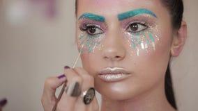 Makijażu artysta maluje wargi piękna dziewczyna, tłuściuchne wargi zbiory