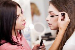 Makijażu artysta robi makeup piękna dziewczyna w piękno salonie obraz royalty free