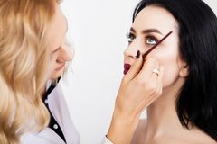 Makijażu artysta robi makijaż dziewczyny w salonie, piękna pojęcie zdjęcie stock