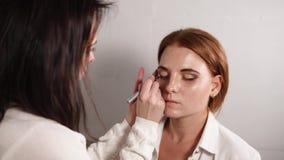 Makijażu artysta rysuje linię na powiece ładny model zdjęcie wideo