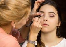 Makijażu artysta stosuje ciekłego eyeliner z muśnięciem piękna kobiety twarz Uzupełniał w procesie obraz stock