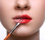 Makijażu artysta stosuje pomadkę z muśnięciem, piękno Obraz Stock