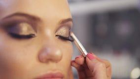 Makijażu artysta stosuje złotego oko cienia makeup wzorcowy ` s ono przygląda się Zamyka w górę widok zbiory wideo