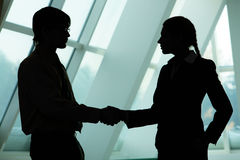 Making agreement. Silhouettes of two business partners handshaking and greeting each other Stock Image