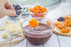 Making apricot and prunes lollipops with chocolate and macadamia nuts Stock Photo
