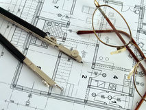 Making architectural plan. Divider and spectacles laying on architectural plan Royalty Free Stock Images