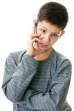 Making arguments while phone talk. A handsome boy is talking on the mobile phone indignantly; isolated on the white background Royalty Free Stock Images
