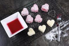 Making Australian style pink heart shape small lamington cakes Royalty Free Stock Image