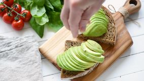 Making healthy avocado toast. Making avocado toast. Person putting sliced avocado on whole grain bread stock video footage