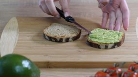 Making avocado toast. Woman spread avocado on toasted sandwich bread. Top view.  stock video