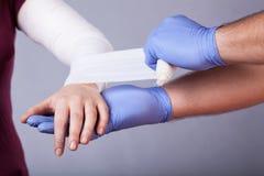Making a bandage. Close-up of paramedic making a bandage for woman royalty free stock photos