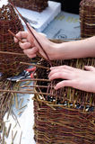 Making basket out of wicker. Photo of woman making basket out of wicker royalty free stock photos