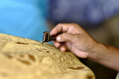 The Making of Batik. Close up of hand during batik making process . Batik is well known original Indonesian craft. Batik also became the greatest legacy Royalty Free Stock Photography
