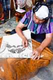 Making a Batik Tapestry. Xijiang, China - July 05:  A traditional woman making a Batik Tapestry in Xijiang, China.  A very traditional technique that is popular Stock Photos