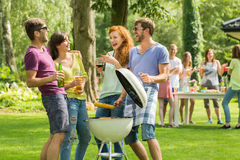 Making bbq together. Two couples laughing during making bbq together stock image