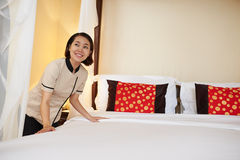 Making bed. Asian maid making bed in hotel room in the morning Stock Images