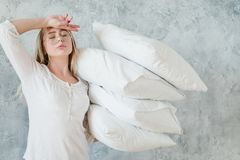 Making bed morning chores tired woman pillows. Making bed. Morning chores concept. Tired woman holding pile of pillows stock image