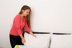 Making bed. Young woman making a bed and puffing the pillows Stock Images