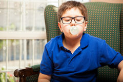 Making big bubble with gum. Blond tween with glasses blowing a bubble with some chewing gum at home royalty free stock photo