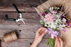 Making a bouquet from gillyflowers and alstroemeria on old woode Royalty Free Stock Images