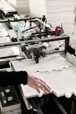 Making boxes on conveyer. Worker Takes Parcel From Moving Belt Conveyor Stock Image