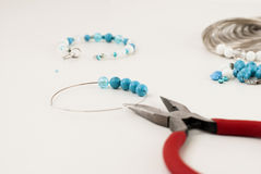 Making a bracelet of turquoise. beads, wire tools. Turquoise and white beads, memory wire for bracelet, tools for creating fashion jewelry in the manufacturing Stock Images