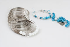 Making a bracelet of turquoise. beads, wire tools. Turquoise and white beads, memory wire for bracelet, tools for creating fashion jewelry in the manufacturing Stock Photos