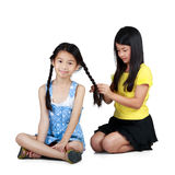 Making braid to cute little girl. Isolated over white Stock Photography