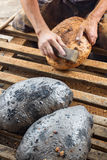 Making bread the traditional way - cleaning away the charred cru. Making bread the traditional way - cleaning the charred crust from an oven baked bread, closeup Royalty Free Stock Image