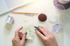 Making brooch. Girl is engaged in creative activity. Making brooch. Flat lay stock photography