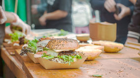 Making of Burgers. A burger waiting to be finished with people in the background Stock Photo