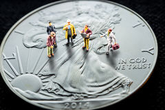 Making business counting on silver, precious metals. Closeup of silver american eagle coin and miniature business men figurines having a meeting Stock Photos