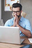 Making business decision every day. Close-up pensive young handsome man wearing glasses working on laptop and keeping hands on chin while sitting at his working Royalty Free Stock Image